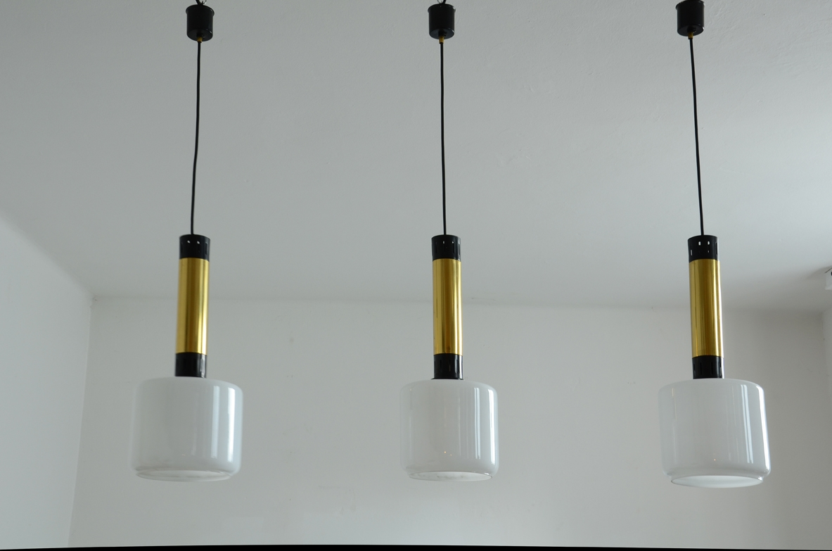 Three elegant Stilnovo suspension lamps with brass structure, lacquered metal and opal glass diffusers.