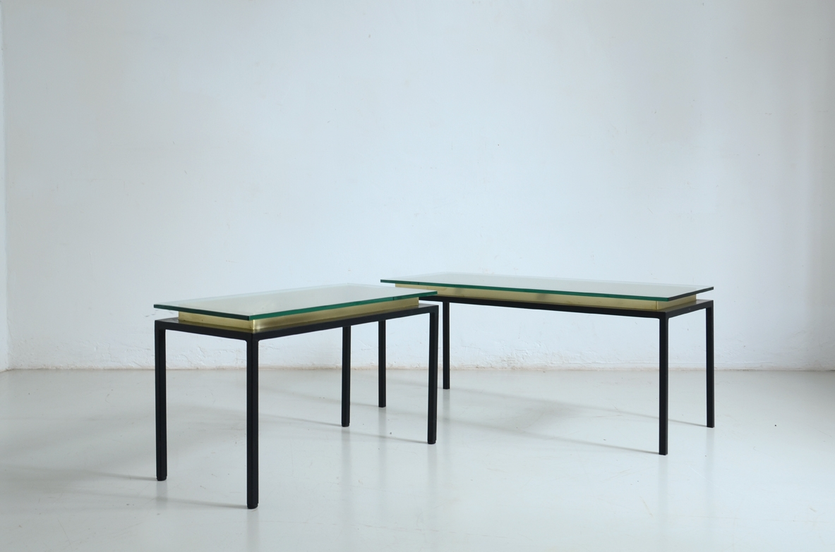 Pair of low tables with satin black metal structure, glass top resting on a brass frame.